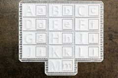 Alphabet printed in 3d on white square tiles. Set of uppercase a. Nd lowercase letters to make typographic tones made with a 3D printer. Maker activity fo stock photography