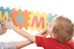Alphabet puzzle pieces on white background. Mother teaches the child to read and write. Education concept stock photos