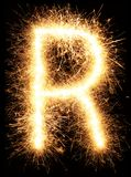 Alphabet R de lumière de feu d'artifice de cierge magique sur le noir Photos libres de droits