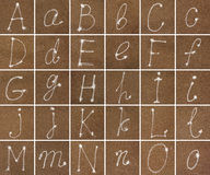 Alphabet in sand from A to O Royalty Free Stock Image