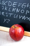 Alphabet scribbles on blackboard with lunch apple Royalty Free Stock Photo