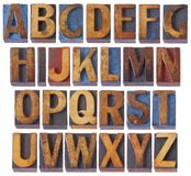 Alphabet set in antique wood type. Complete English alphabet set - collage of 26 isolated vintage wood letterpress printing blocks, scratched and stained by blue stock photo