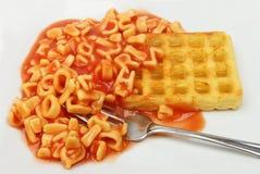 Alphabet spaghetti and potato waffle. Closeup of alphabet spaghetti and a potato waffle with a fork on a plate Stock Images