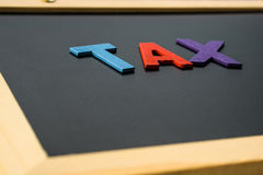 Alphabet TAX in black board, finance concept Stock Photo