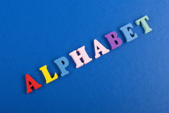 ALPHABET word on blue background composed from colorful abc alphabet block wooden letters, copy space for ad text. Word on blue background composed from colorful Stock Photos