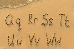 Alphabet written by hand on sandy beach Stock Photography