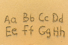 Alphabet written by hand on sandy beach Stock Photo