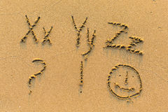 Alphabet written by hand on sandy beach Royalty Free Stock Photography