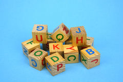 Alphabetical wooden cubes stack on blue background Royalty Free Stock Images