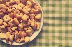 Alphabetplätzchen Kekse auf Plaidmuster Stockfoto