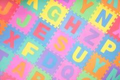 Alphabetpuzzlespielzeichen deckt Hintergrund mit Ziegeln Stockfotos