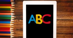 Alphabets on tablet PC by color pencils. Digital composite of Alphabets on tablet PC by color pencils Royalty Free Stock Image