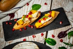 Alphonso mango Toasts of cheese. Bruschetta with mango and cheese. Homemade. Healthy vegetarian nutritionon a wooden background, royalty free stock photography