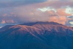 Alpi australiane in luce arancio di tramonto e nuvole basse Fotografia Stock