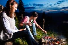 Alpi - coppie a fuoco di accampamento in montagne Fotografia Stock