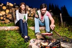 Alpi - coppie a fuoco di accampamento in montagne Fotografia Stock Libera da Diritti