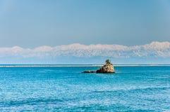 Alpi del Giappone dietro una piccola roccia nel mar del Giappone Fotografia Stock