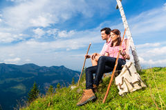 Alpi - facendo un'escursione le coppie le prese irrompono le montagne Immagine Stock