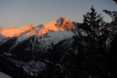 Alpi francesi durante il tramonto contro il cielo blu scuro con un villaggio nella valle Fotografie Stock