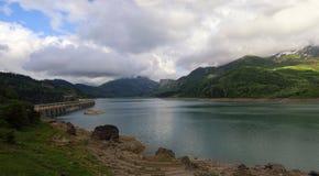 Alpi francesi: lago artificiale della montagna, una diga Immagine Stock