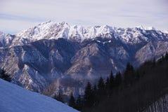 Alpi italiane con neve in un giorno soleggiato nei precedenti di una valle Immagine Stock