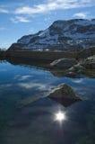 Alpi: riflessione del sole nel lago della montagna Fotografia Stock Libera da Diritti