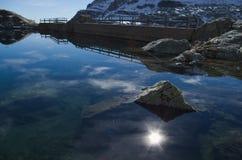 Alpi: riflessione del sole nel lago della montagna Fotografie Stock