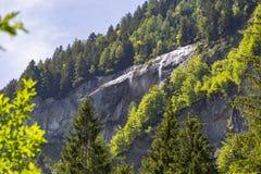 Alpi svizzere viste attraverso foresta in Blausee o nel parco naturale blu del lago, Svizzera Immagine Stock Libera da Diritti