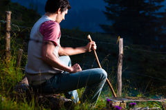 Alpi - uomo a fuoco di accampamento in montagne bavaresi Fotografie Stock