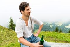 Alpi - uomo in montagne che beve birra dalla bottiglia Fotografie Stock