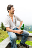 Alpi - uomo in montagne che beve birra dalla bottiglia Fotografia Stock