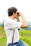 Alpi - uomo sulle montagne con i binocoli Immagini Stock