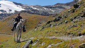 Alpien landschap met ruiter in langzame motie stock video