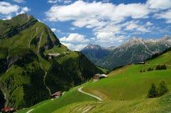 Alpien landschap met verspreide huizen op een helling stock fotografie