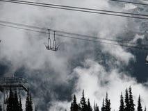 Alpien landschap van wolken en skilift stock afbeeldingen