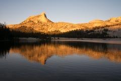 Alpiene die Gloed op Kathedraalpiek in het meer wordt weerspiegeld stock foto