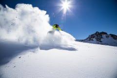 Alpiene skiër op piste, die bergaf ski?en Stock Foto's