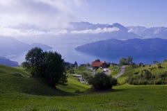 Alpiene weide met buitenhuis Stock Afbeelding