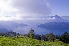 Alpiene weide met meer bij rug Stock Fotografie