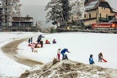 Alpin barn` s skidar skolan Instruktör- och barnstudenter i färgrikt skidar utrustning royaltyfri bild