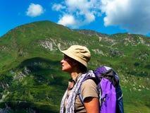 _ alpin Berg En flicka med en ryggsäck ser vaggar arkivbild