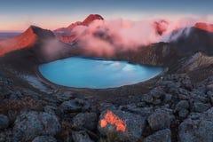 alpin crossingtongariro Ottasoluppgång, landskaplandskap av den blåa sjön, lösa berg och enorm vulkan royaltyfri foto