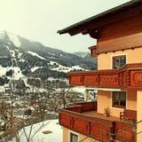 Alpin hus med träbalkongen i vinterbergbyn, fjällängar Arkivfoto