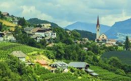 Alpin by i den gröna dalen bland bergen Arkivfoton