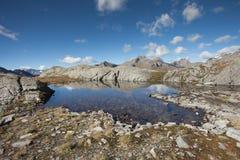 Alpin sjö i fjällängarna på nedgången Arkivfoto