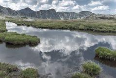 Alpin sjöspegel som reflekterar sommarhimlarna Royaltyfri Fotografi