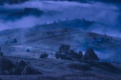 Alpin by som t?ckas med djup dimma p? natten arkivbilder