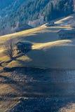 Alpin-Weide mit grünem Gras und einigen Kabinen lizenzfreies stockbild
