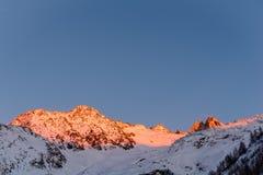 Alpina bergkanter som är upplysta i guld- timme i vinter Arkivfoto
