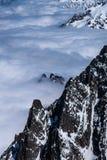 Alpina bergkanter som överst dyker upp till och med molnräkningen Royaltyfri Bild
